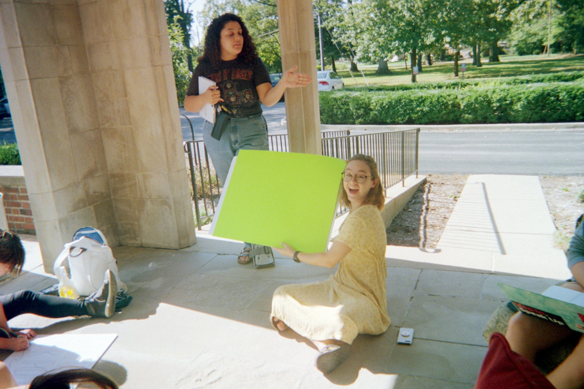 Hannah holding up her sign, with Lizzy in the background.