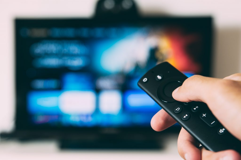 Photo of a hand holding a remote, and a blurry TV screen in the background.