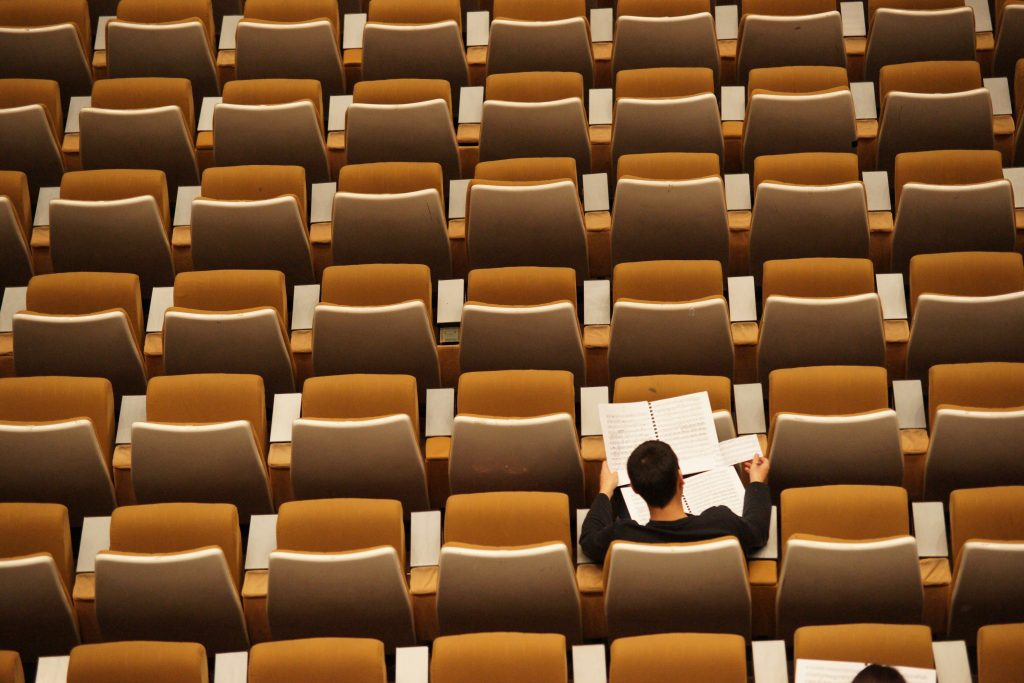 Photo of a person studying in an empty lecture hall. By Philippe Bout.