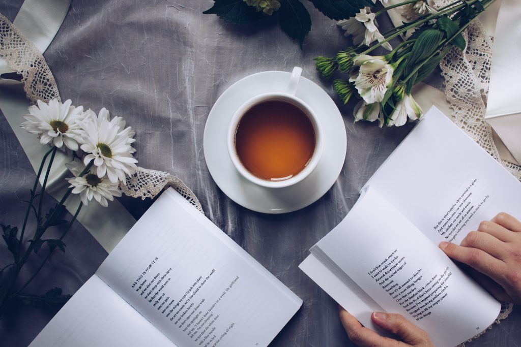 A book laid open. Next to it, a cup of tea and some dried flowers.